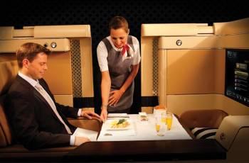 Ein First Class Reisender wird in der Diamond First Class Suite von Etihad Airways von einer Stewardess bedient.