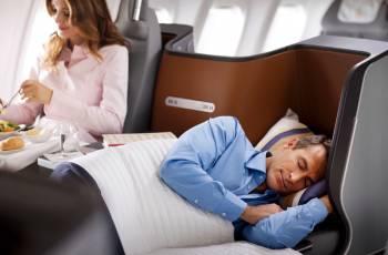 Ein Mann schläft im neuen Lufthansa Business Class Sitz, der zum Bett umfunktioniert ist.